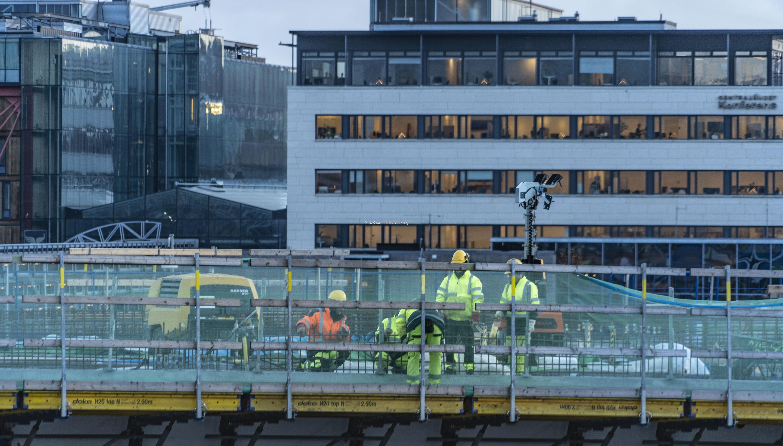 Jobbare på Hisingsbron. I bakgrunden syns en kontorsfastighet och i fönstren har man pyntat med ljusstakar.