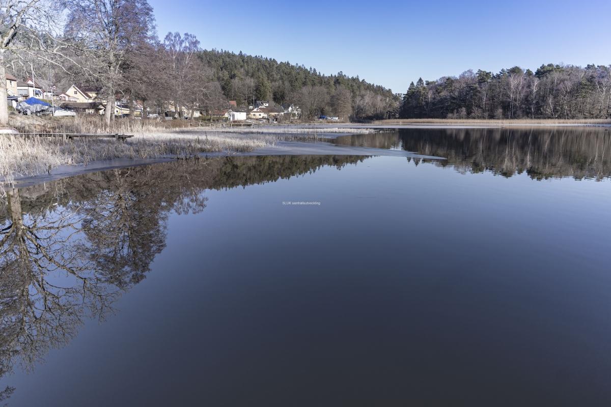 Det är klart och lite kallt väder. Solen lyser och det blir speglingar i Landvettersjön.