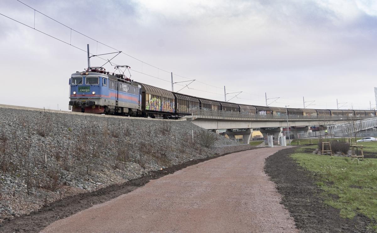 Hamnbanan går parallellt med Partihallsförbindelsen. Ett långt godståg är på väg mot Göteborgs Hamn.