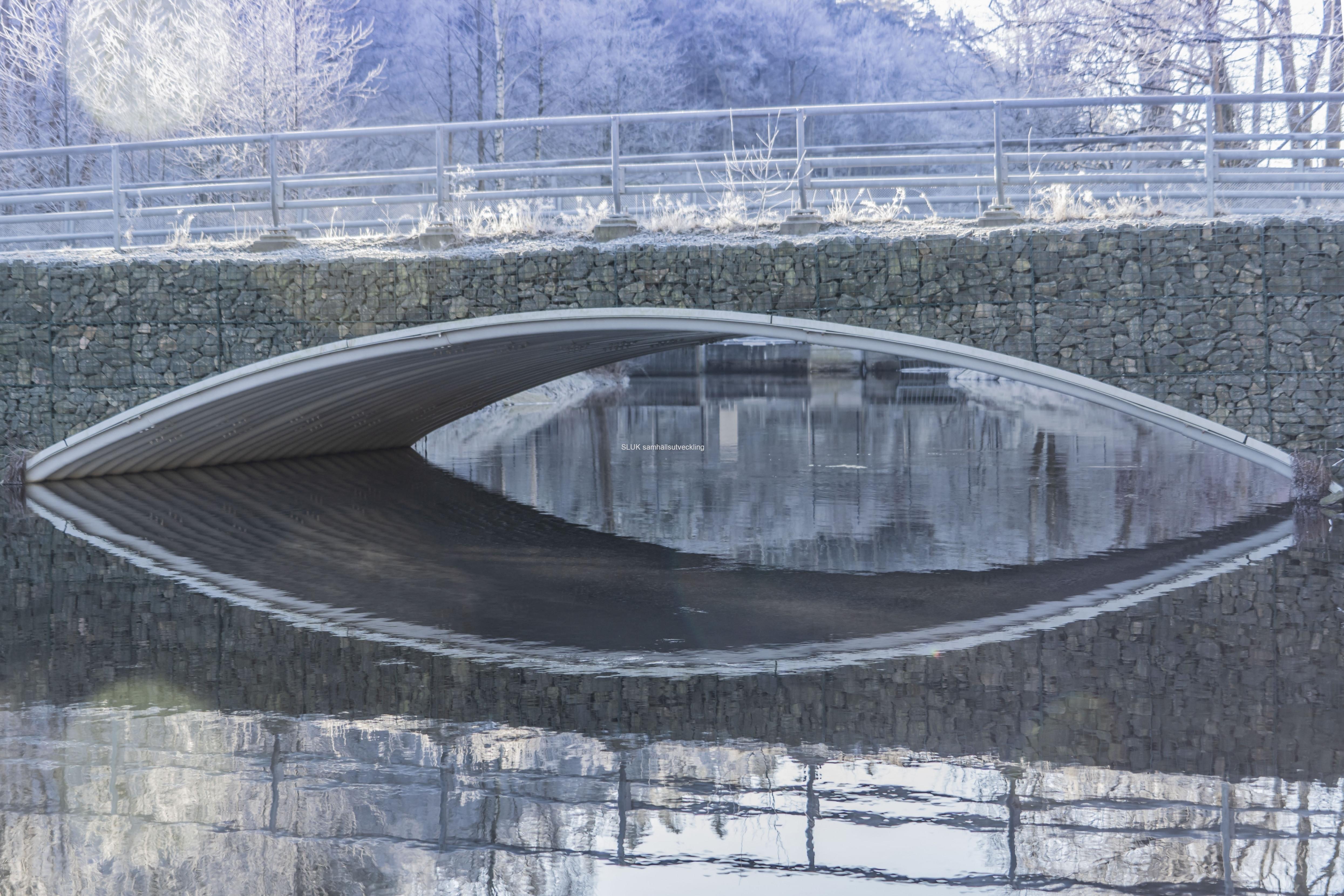 Stenbron, som man skulle tro är gammal, men är relativt ny, speglas i sjön.