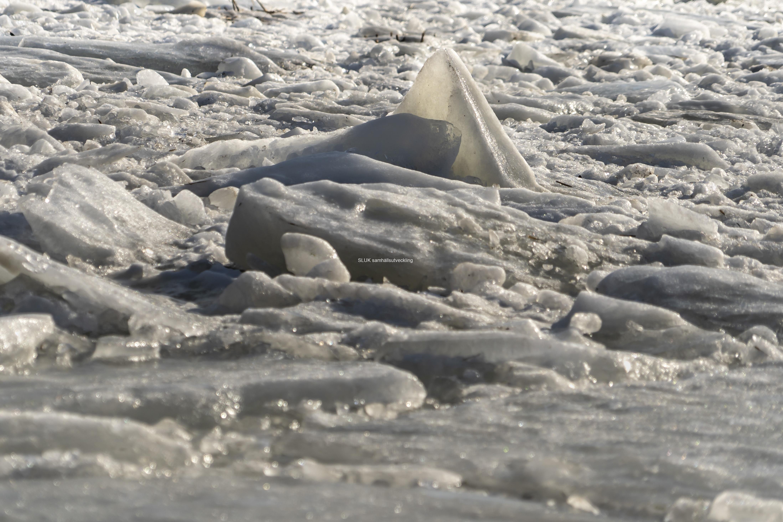 Vid kajen ligger bruten is i stora block