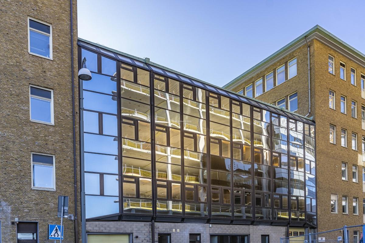 På glasfasaden mittemot pågående byggnation, blir det speglingar av bygget.